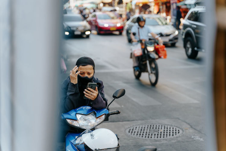 Biker in Bangkok wearing a mask is looking at his smartphone Transportation Mode Of Transportation One Person City Wireless Technology Real People Technology Street Land Vehicle Car Motor Vehicle Holding Mobile Phone Lifestyles Communication Connection Architecture Leisure Activity Smart Phone Outdoors Smartphone Motorbike City Bangkok Thailand Smog Pollution