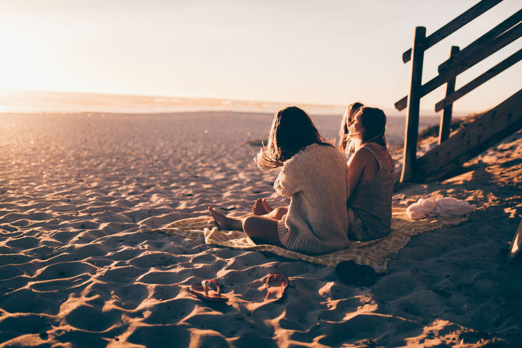 Two People Sand Sitting Leisure Activity Togetherness Relaxation Beach Lifestyles Rear View Sky Nature Adult Vacations Trip Women Holiday Sunset Emotion Real People Couple - Relationship Positive Emotion Outdoors
