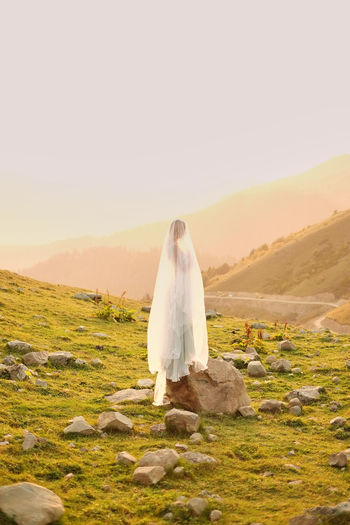 Low Section Of Woman Standing On Mountain During Sunset