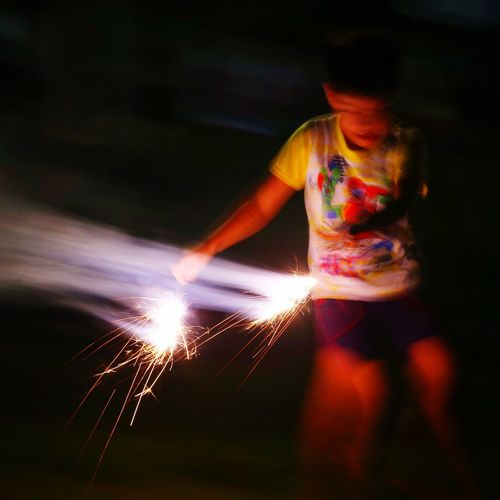 A boy playing with fire sparkles during the mid-autumn festival in Singapore Fire Mid Autumn Festival Mid Autumn Sparkles Night Festival