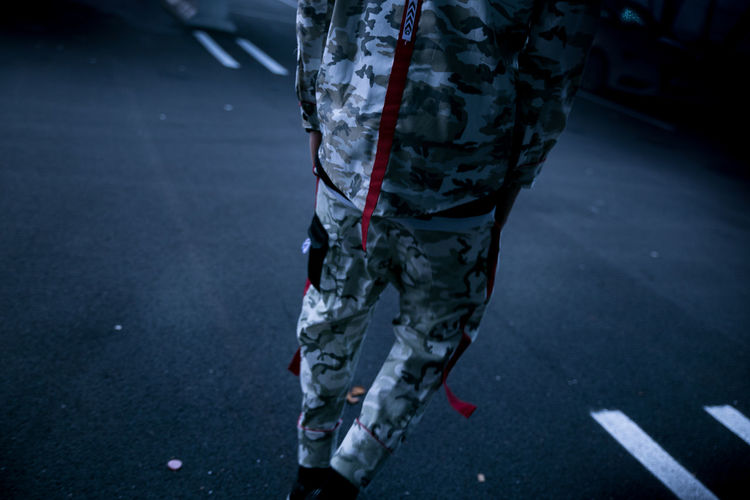 Rear View Of Man In Camouflage Clothing Walking On Street