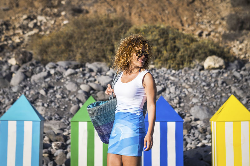 Mature woman with curly hair standing against rocky hill