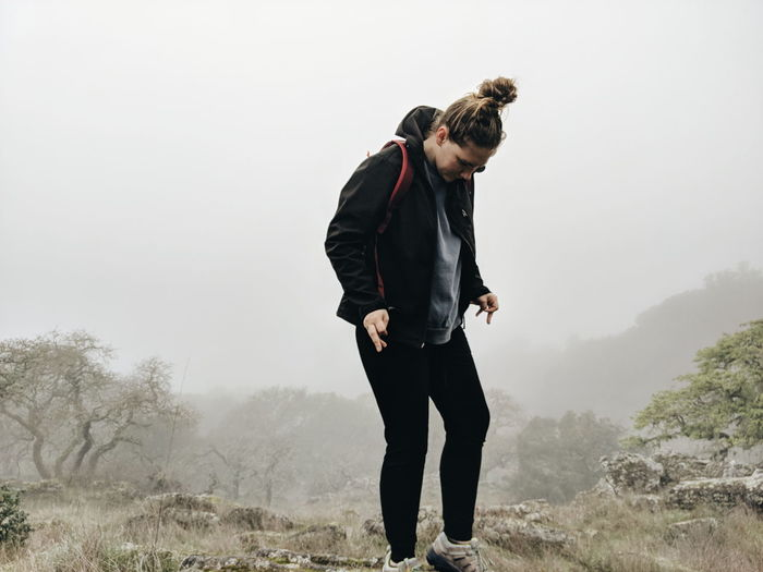 Young Woman Standing On Field In Foggy Weather On Rock