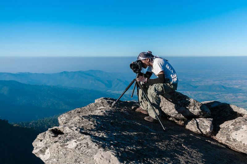 Full length of man photographing while sitting at cliff against landscape