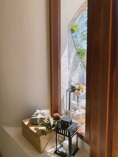 Flower vase on table by window at home