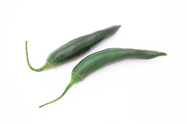 Close-up of green chili pepper against white background