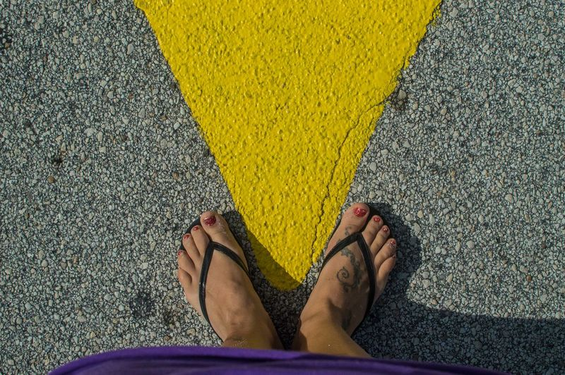 Low Section Of Woman Wearing Slippers Standing On Road