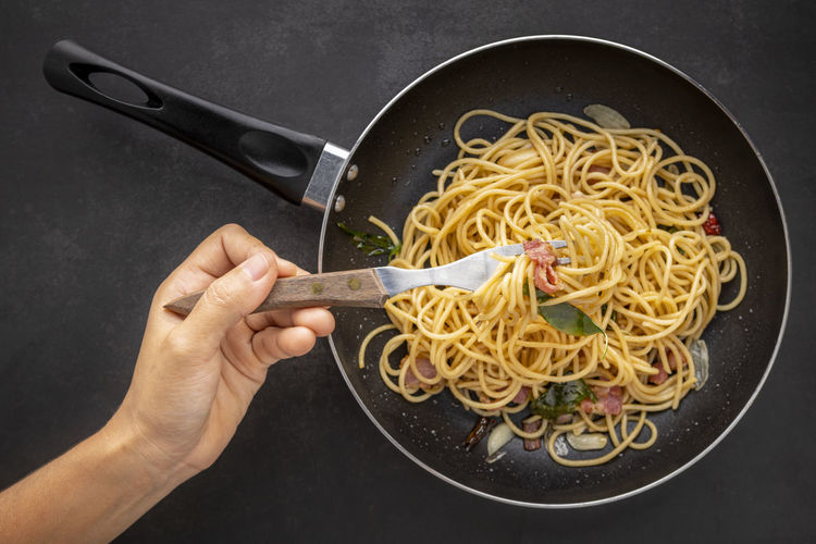 Hand holding fork get spaghetti pasta with dried chilli, garlic, sweet basil and bacon in black pan