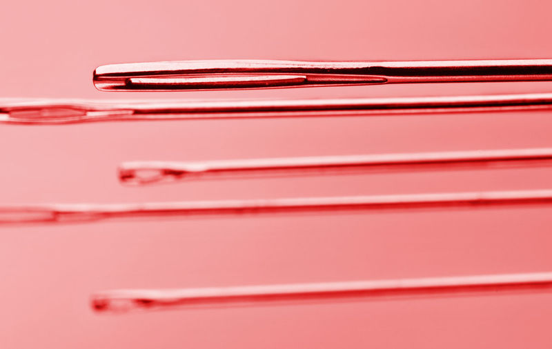 Sewing needles studio shot , red color , graphic composition Red Close-up Studio Shot Colored Background No People Still Life Group Of Objects Sewing Needle Tools Steel Fantasy Equipment Eyelets Selective Focus Tailor Creativity Long Small Straight Sewing Abstract Space For Text Reflections Instruments In A Row