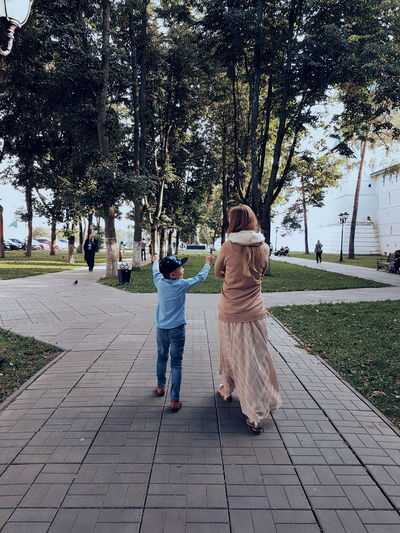 Mother And Son Walking On Footpath Against Trees In Park