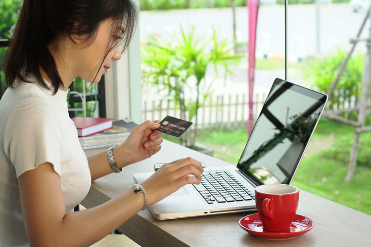 Young woman holding credit card while using laptop at home