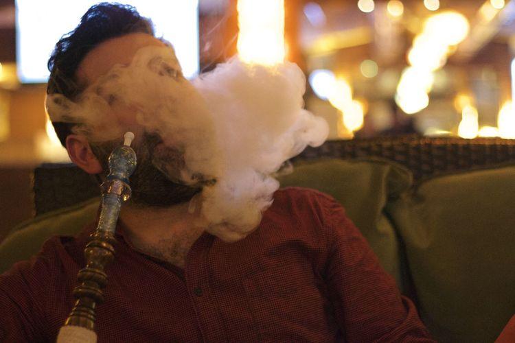 Man smoking hookah while sitting at restaurant