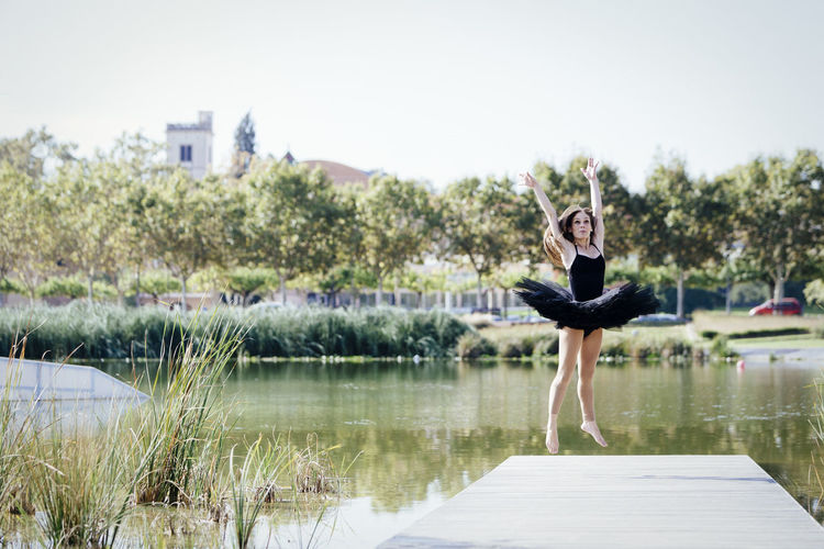 Woman Ballet Dancing On Pier Over Lake