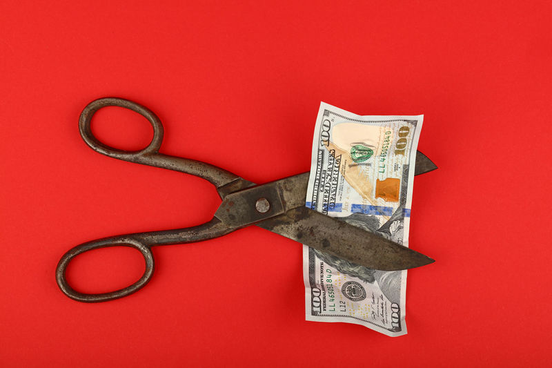 Old vintage scissors cut jammed USD 100 banknote over red background, elevated top view American Banknote Close-up Crisis Currency Cut Danger Devaluation Dollar Economy Elevated View Exchange Finance Hand Tool Inflation  Money Paper Money Rate Recession Red Red Background Scissors Threat USA Warning