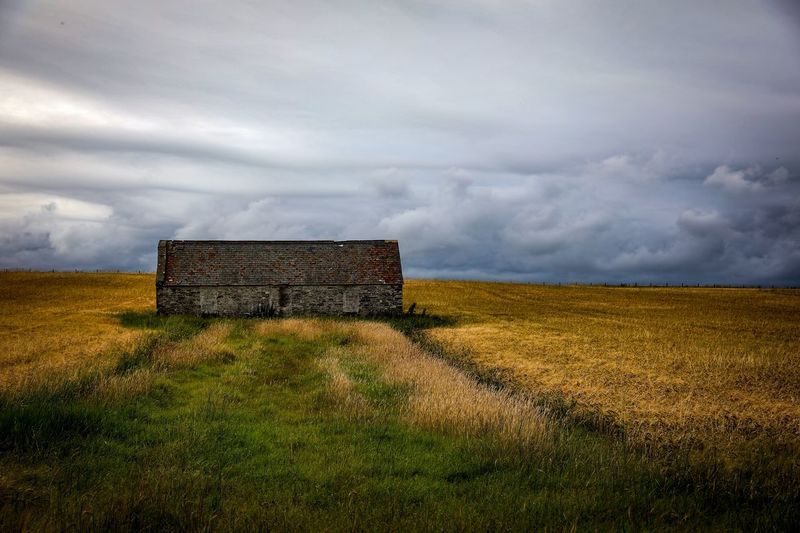 Abandoned house on field against storm clouds