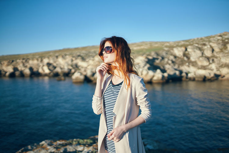 Woman wearing sunglasses standing by sea against sky
