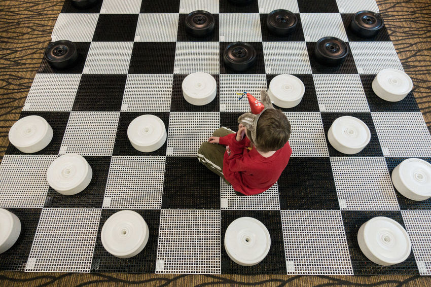 even when he's not trying, he beats me at all board games Boy Checkerboard Checkers Chess Board High Angle View Indoors  Life Size  One Person Play Sitting