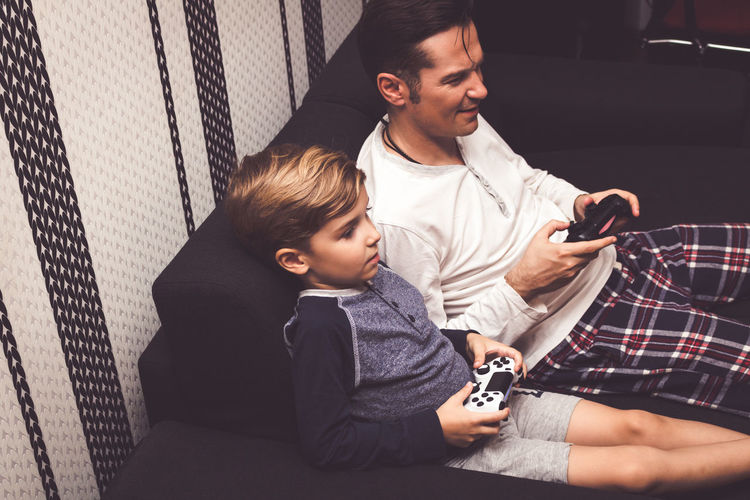 Father and son sitting on mobile phone
