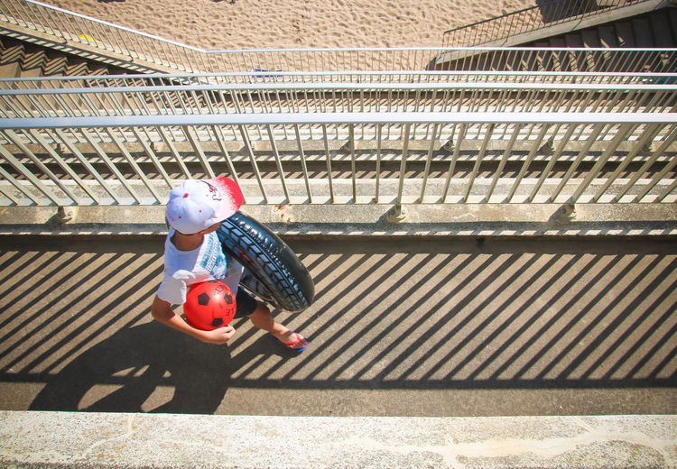 High angle view of boy with ball and tire walking on footbridge