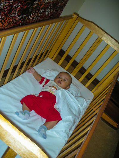 Cute baby boy lying in crib at home