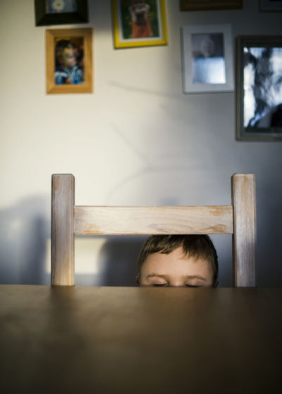 Boy Hiding Behind Table At Home