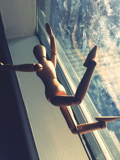 Low angle view of figurine in mid-air by window at home