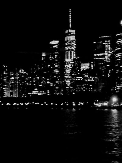 New York at Night New York City New York At Night Architecture Building Building Exterior Built Structure City Cityscape Dark Financial District  Illuminated Modern Nature Night No People Office Building Exterior Outdoors Sky Skyscraper Spire  Tall - High Tower Travel Destinations Water Waterfront