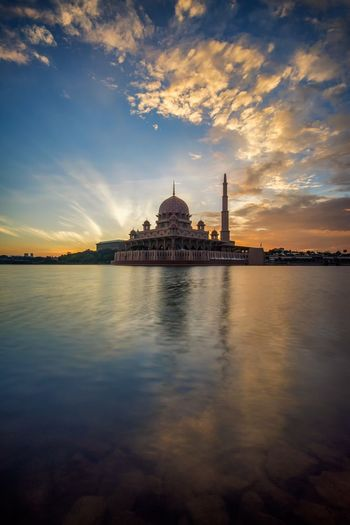 Putra mosque by lake against sky during sunset in city