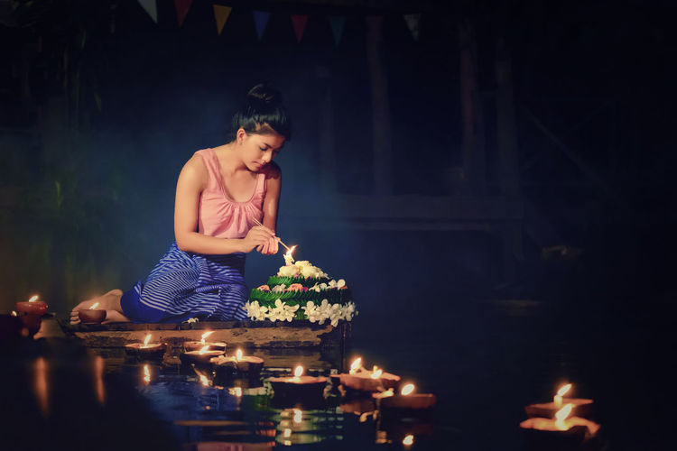 Loy Krathong Traditional Festival, Thai woman hold kratong, Thailand, Asia woman in Thai dress traditional hold kratong and bring Krathong to float in Loi kratong day of Thailand. Beautiful Woman Burning Candle Flame Flower Front View Illuminated Indoors  Lifestyles Night One Person People Real People Table Young Adult