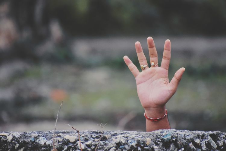 Cropped hand waving behind retaining wall