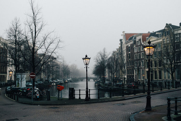 Canal amidst buildings against sky during winter
