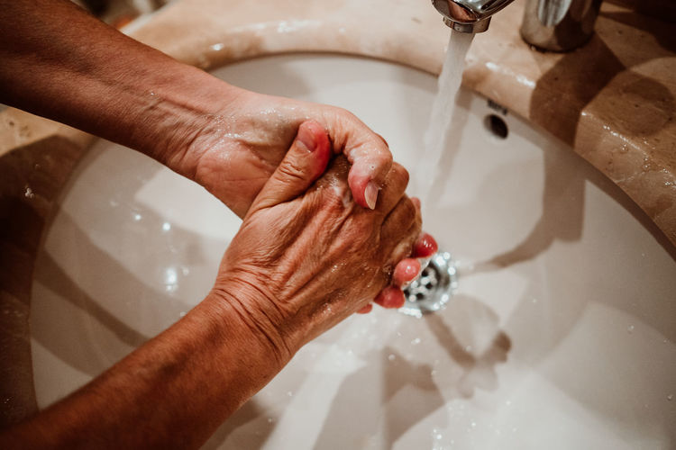 Cropped image of person washing hands in sink