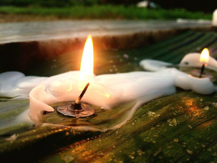 Close-Up Of Illuminated Candle On Wood