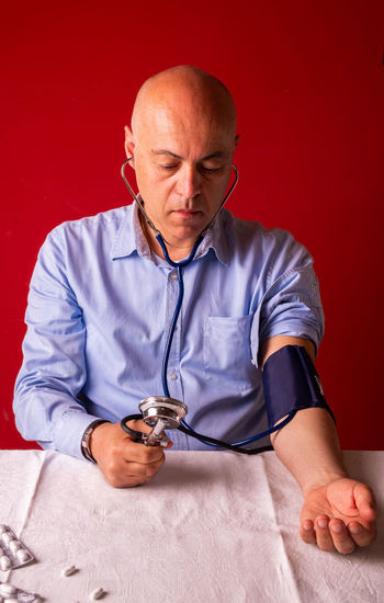 Man checking blood pressure at table against red wall