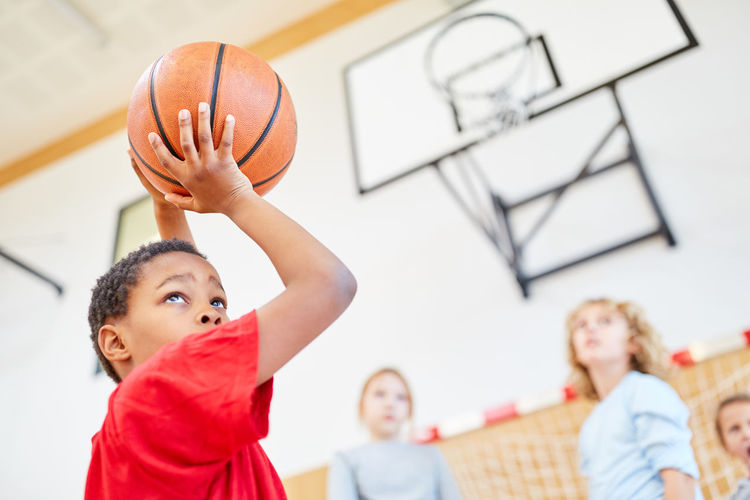 Close-up of boy playing with basket ball