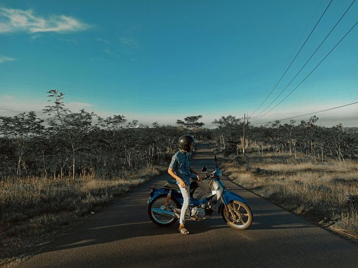 Bicycles riding motorcycle on road against sky