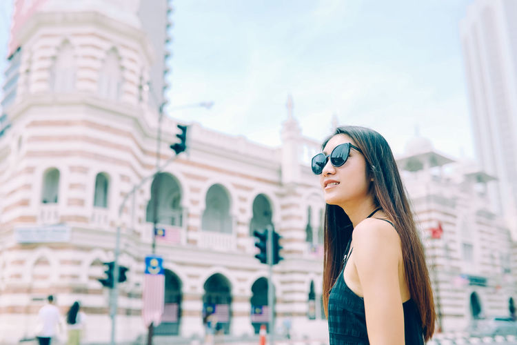 Young Woman Wearing Sunglasses Standing Against Historic Building