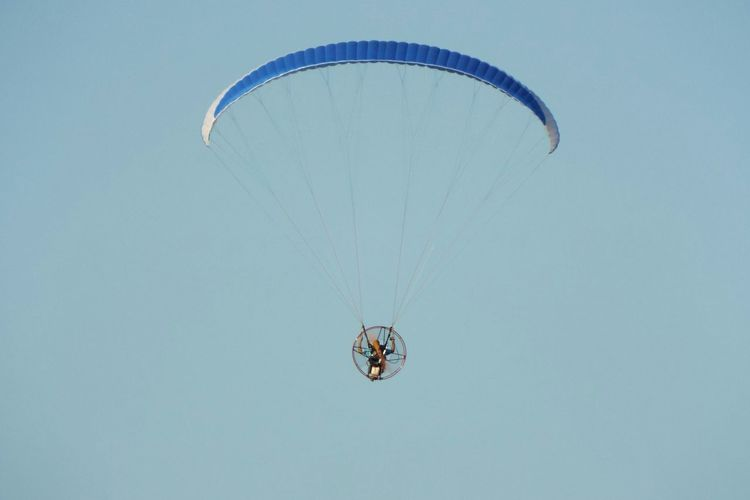 Low angle view of person flying powered hang glider in clear sky