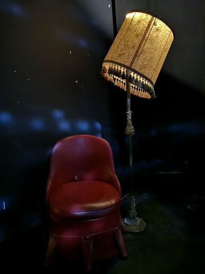 Illuminated electric lamp by chair