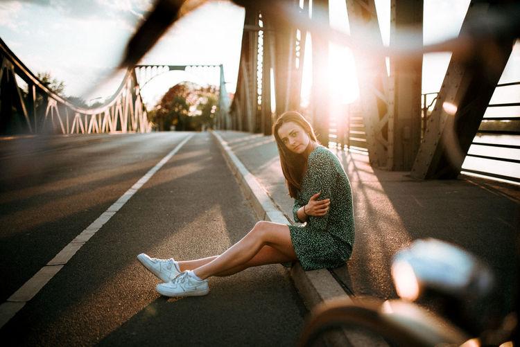 Woman sitting on bridge