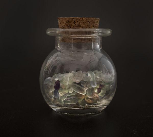Close-up of medicines in glass jar against black background