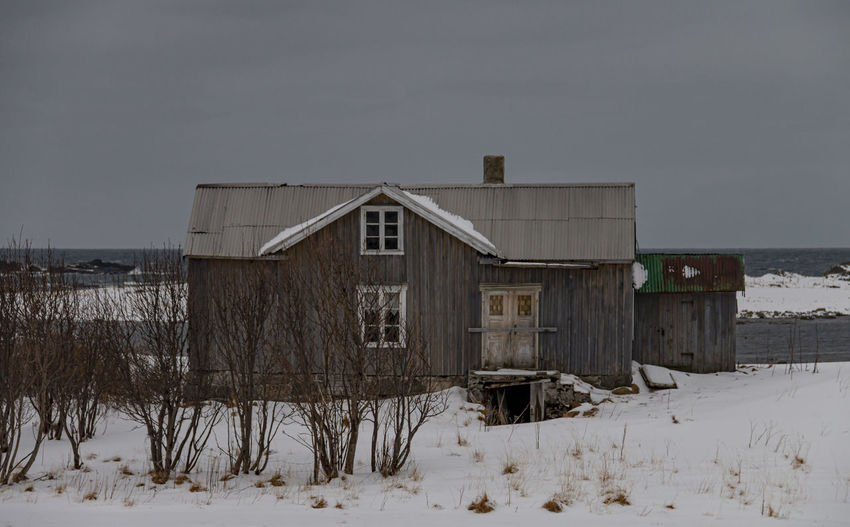 Abandoned house on snow covered field against sky