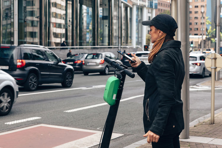 Woman renting an electric scooter using a mobile phone for the payment along a city road