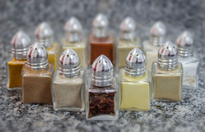 Close-Up Of Spices Arranged In Glass Containers On Marble