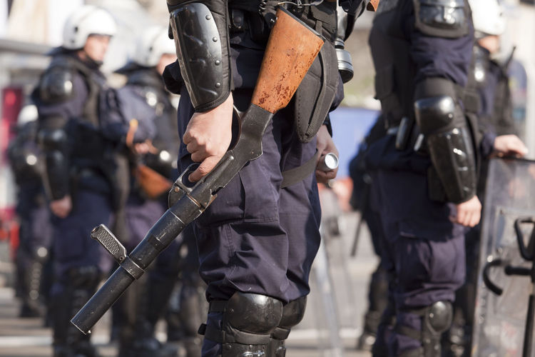 Armed police officers on a duty. Police Officer Policeman Authority Duty Gun Helmet Law Law Enforcement Machine Gun Men Police Police Force Police Uniform Protecting Protection Protective Workwear Public Order Real People Rifle Safety Security Shield Terrorism Uniform Weapon