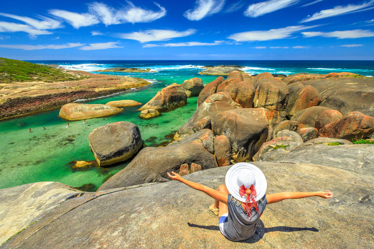 High angle view of woman on rocks by sea against sky