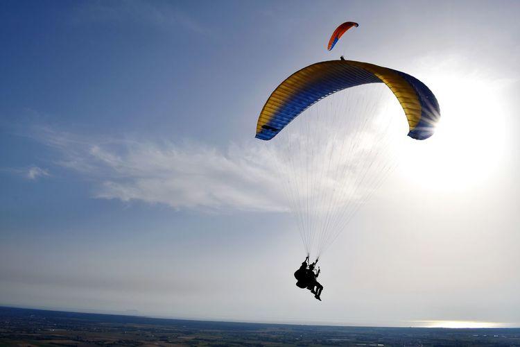 Person paragliding over landscape against sky