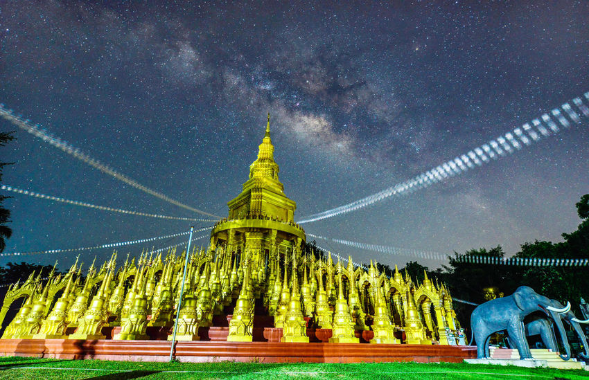 The Milky way over beautiful at wat pasawangboon ,Saraburi, Thailand Milky Way Architecture Astronomy Building Exterior Galaxy Gold Colored Low Angle View Milky Way Nature Night No People Outdoors Pasawangboon Place Of Worship Religion Sculpture Sky Spirituality Statue Tree Water
