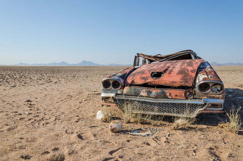 Abandoned Wreck Of Car In Namib Desert Of Angola Against Clear Sky