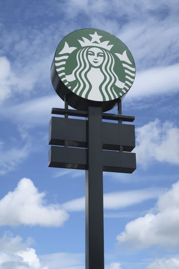 Starbucks marque logo in front of a Starbucks drive through, showing the logo of Starbucks Coffee Company on a blue sky Drive Thru Starbucks Coffee Cloud - Sky Day Drive Through Low Angle View Marque Logo Outdoors Sky Starbucks